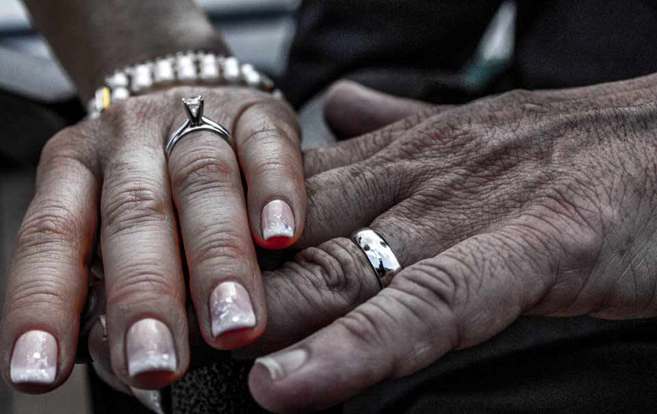 Hands crossed showcasing wedding rings
